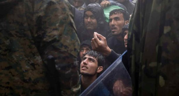 Migrantai ir pabėgėliai prašo makedonų policininkų leisti jiems pereiti sieną iš Graikijos į Makedoniją liūties metu, netoli Graikijos Idomenio kaimo, 2015 m. rugsėjo 10 d.